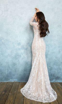 Свадебное платье цвета слоновой кости с облегающим кроем и длинным плотным рукавом.