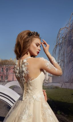 Бежевое свадебное платье с тонким рукавом и объемной отделкой из белого кружева.