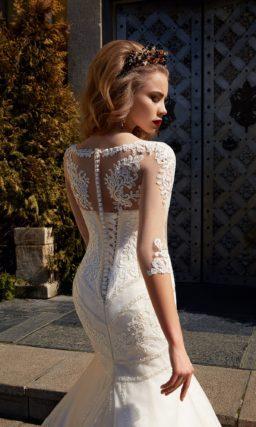 Облегающее фигуру свадебное платье с длинным рукавом и потрясающей фактурной отделкой.
