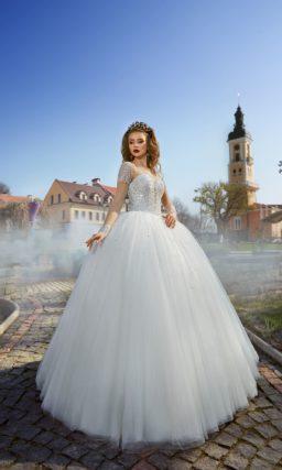 Пышное свадебное платье с многослойной юбкой и расшитым пайетками корсетом с длинным рукавом.