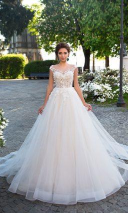 Пышное свадебное платье на кремовой подкладке, с фактурным корсетом и коротким рукавом.