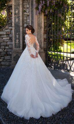 Роскошное свадебное платье с пышной юбкой, украшенной кружевом и шлейфом сзади.