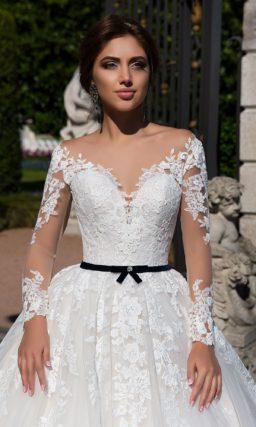 Пышное свадебное платье с кружевной отделкой и узким черным поясом на линии талии.