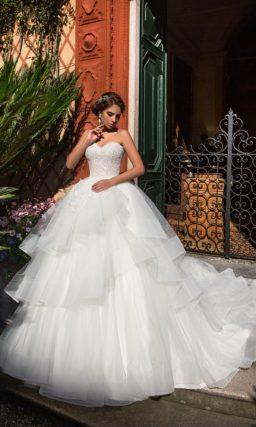 Открытое свадебное платье с пышной многоярусной юбкой, дополненной сзади шлейфом.