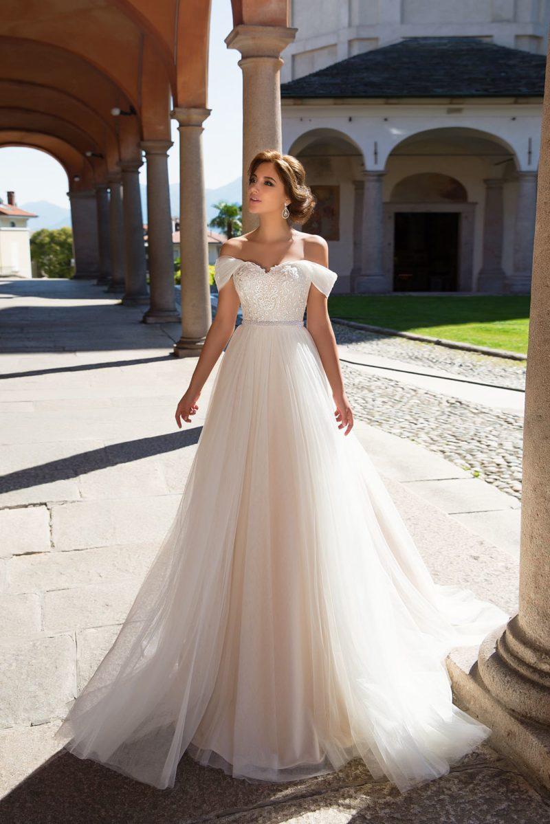 Прямое свадебное платье на кремовой подкладке с узким поясом и бретелями на предплечьях.