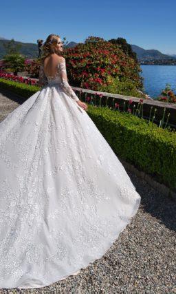 Царственное свадебное платье пышного кроя с портретным декольте и длинными рукавами.