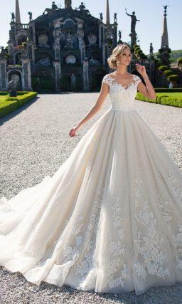 Пышное свадебное платье цвета слоновой кости, романтично украшенное цветочными аппликациями.