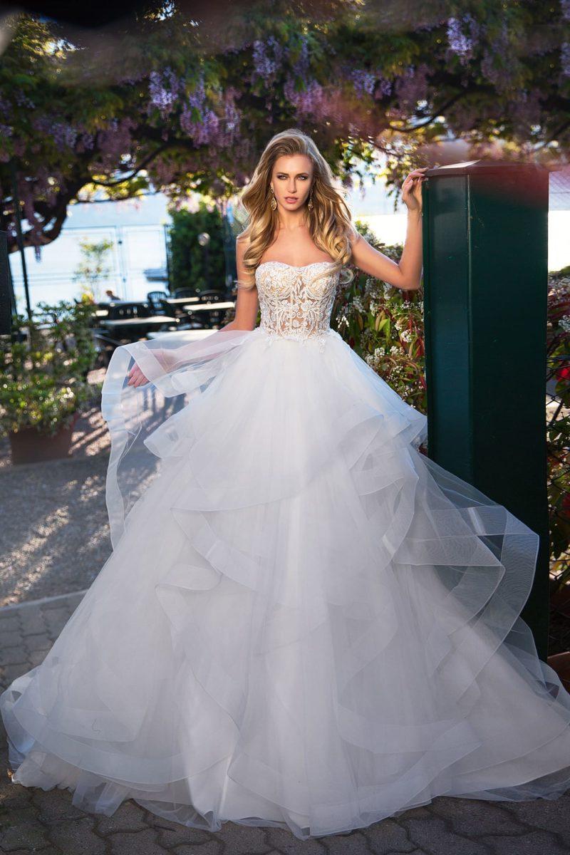 Пышное свадебное платье с многоярусным подолом и чувственным корсетом из кружева.