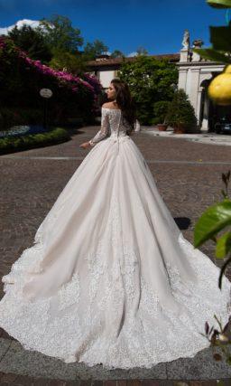 Пышное свадебное платье с эффектным портретным вырезом и рукавами из кружевной ткани.