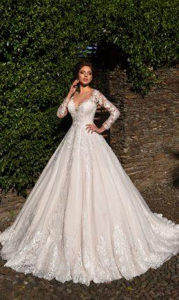 Пышное свадебное платье с длинным рукавом и глянцевыми аппликациями по низу подола.