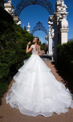 Романтичное свадебное платье с пышными ярусами ткани на юбке и кружевным корсетом.