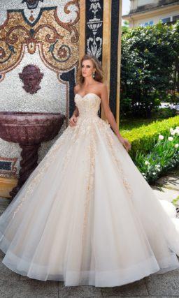 Свадебное платье персикового оттенка с пышной многослойной юбкой и открытым лифом.