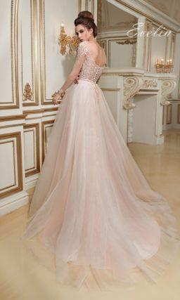 Романтичное свадебное платье пышного кроя с полупрозрачным корсетом и кремовой юбкой.