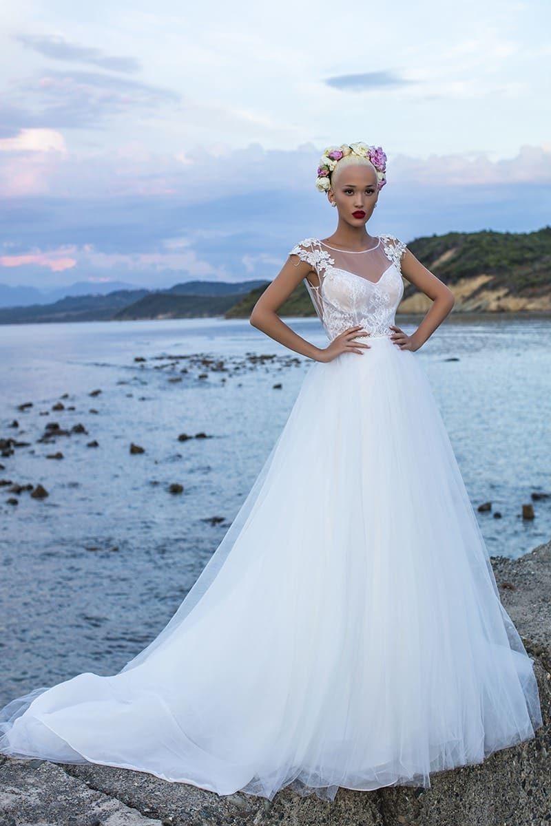 Свадебное платье с полупрозрачным закрытым верхом и многослойной юбкой со шлейфом сзади.