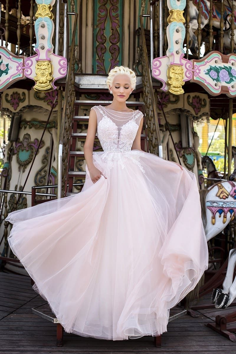 Свадебное платье пастельного розового оттенка с многослойной прямой юбкой и закрытым лифом.