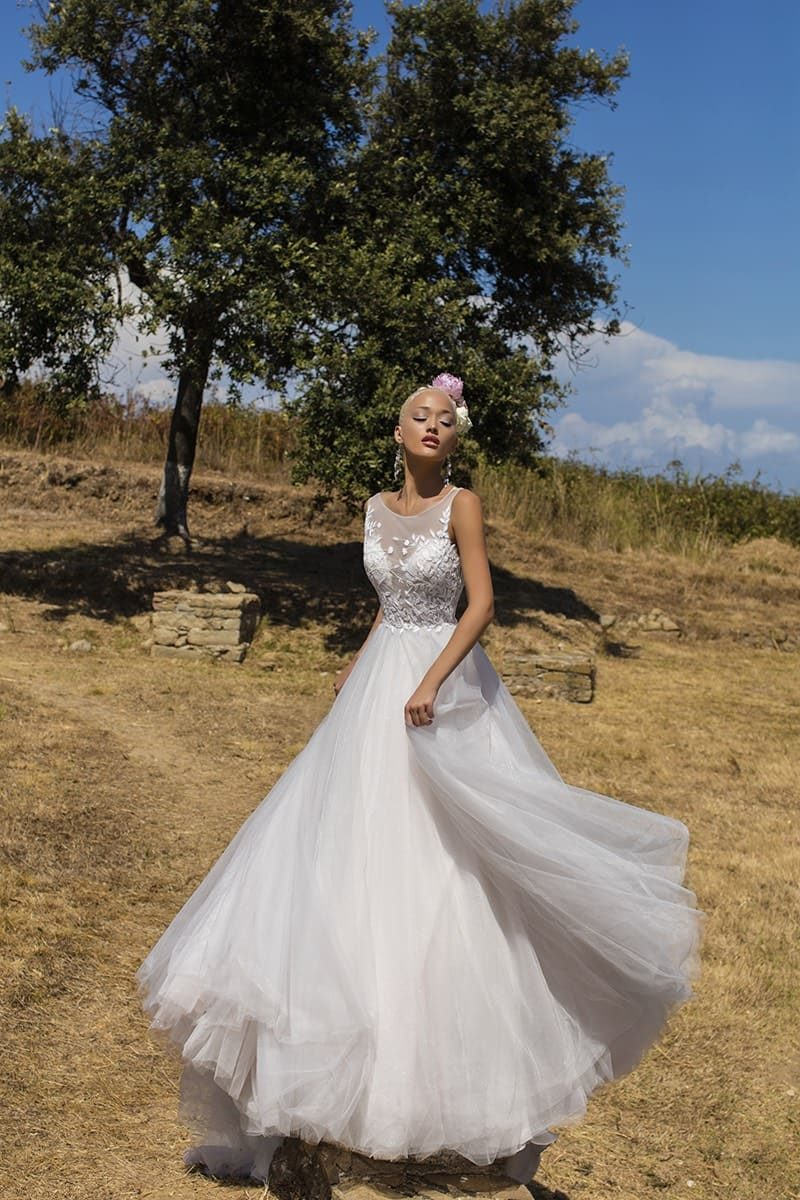 Закрытое свадебное платье с многослойным низом и полупрозрачным лифом с цветочной вышивкой.