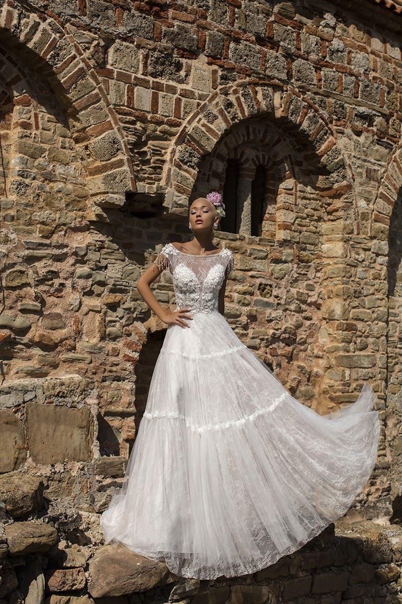Кружевное свадебное платье с юбкой А-силуэта  и эффектным оформлением лифа с коротким рукавом.