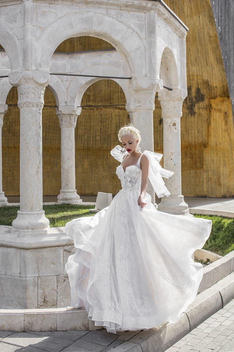 Необычное свадебное платье с многослойной кружевной юбкой и объемной пелериной на плечах.