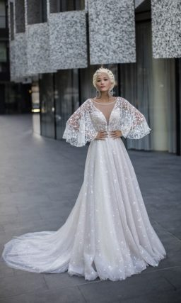 Стильное свадебное платье с широким прозрачным рукавом и сияющей вышивкой по юбке.