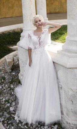 Пышное свадебное платье с эффектным полупрозрачным рукавом и кружевной отделкой.