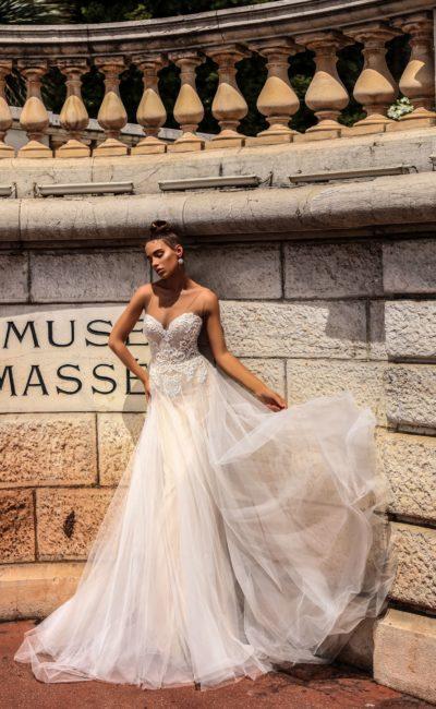 Бежевое свадебное платье прямого кроя с открытым лифом и кружевной отделкой корсета.