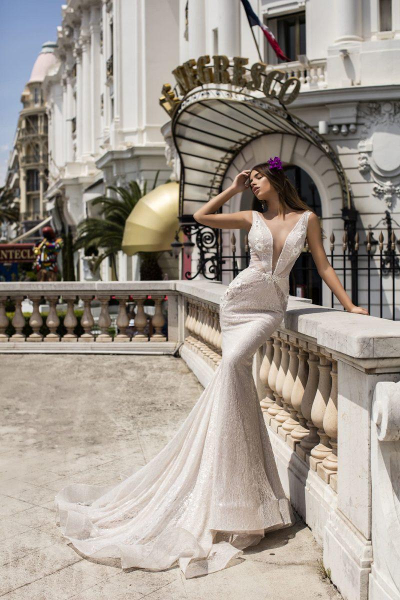 Облегающее свадебное платье «русалка» с длинным шлейфом и глубоким V-образным декольте.