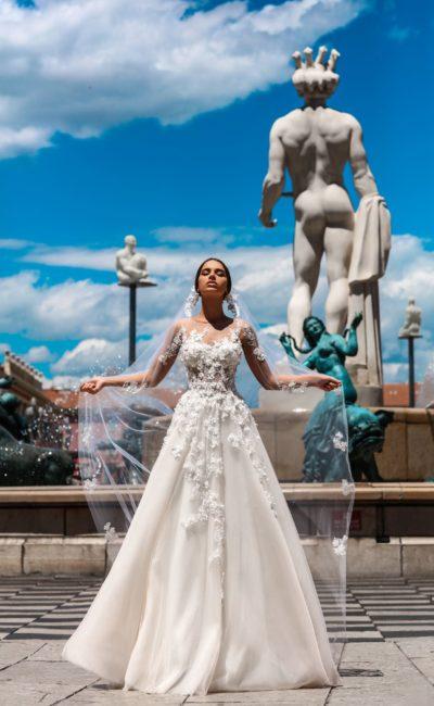 Пышное свадебное платье с полупрозрачным корсетом, длинным рукавом и объемной отделкой.