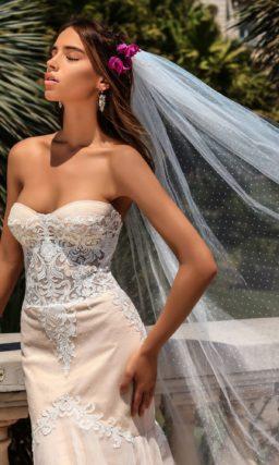 Бежевое свадебное платье с женственным вырезом декольте и роскошным полукругом шлейфа.