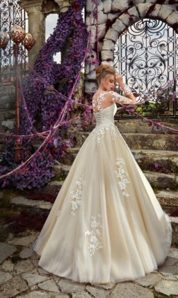 Золотистое свадебное платье А-силуэта с полупрозрачным рукавом и кружевными аппликациями.