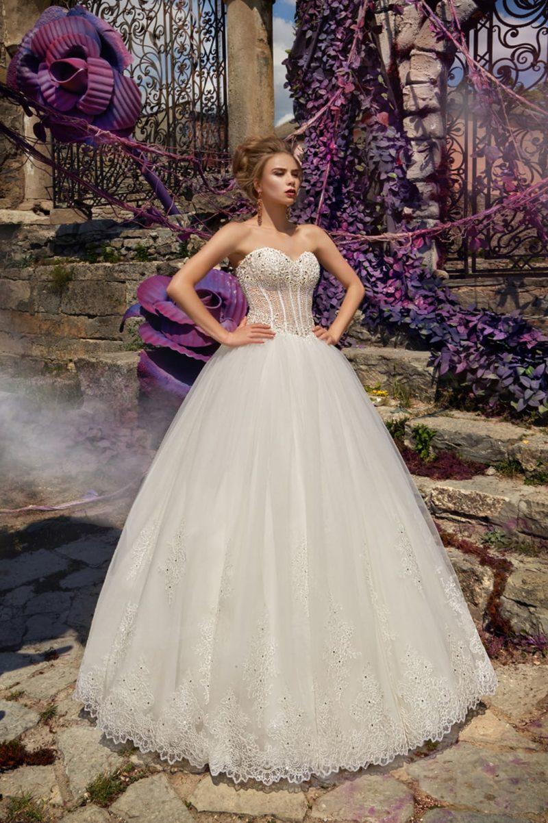 Пышное свадебное платье с открытым лифом в форме сердца и полупрозрачным вышитым корсетом.