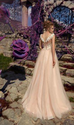Кремовое свадебное платье с эффектным глубоким вырезом и объемной отделкой по корсету.