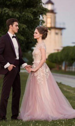 Нежное свадебное платье розового цвета с отделкой из аппликаций и изящным коротким рукавом.