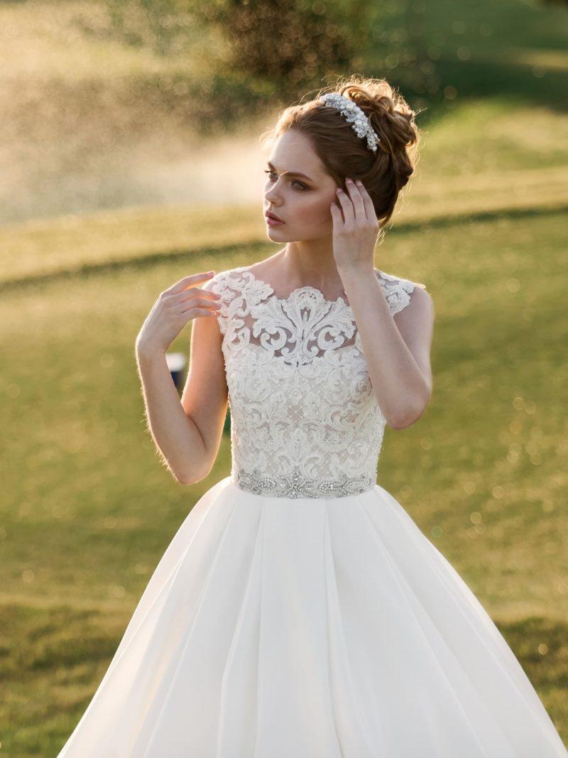 Пышное свадебное платье с лаконичной юбкой и кружевной отделкой закрытого лифа.
