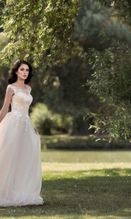 Кремовое свадебное платье с деликатным вырезом на лифе и кружевными аппликациями отделки.