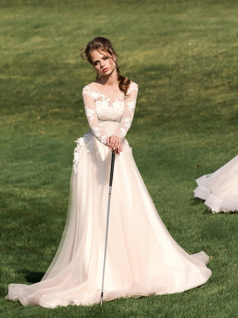 Кремовое свадебное платье с прямой юбкой и длинным рукавом из полупрозрачной ткани.