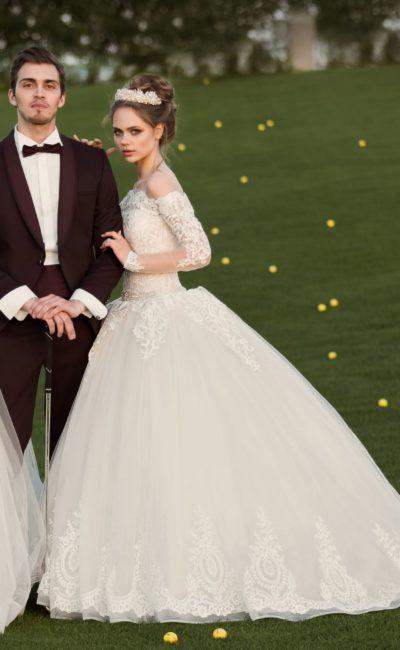 Пышное свадебное платье с портретным декольте и облегающими полупрозрачными рукавами.