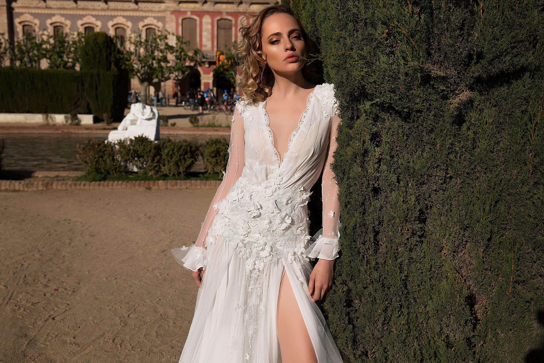Прямое свадебное платье с чувственным разрезом, полупрозрачным рукавом и объемным декором.