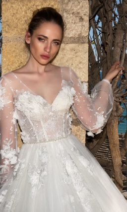 Изысканное свадебное платье пышного силуэта с объемным декором и полупрозрачным рукавом.