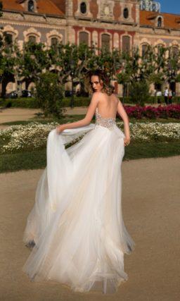 Прямое свадебное платье с открытым бежевым корсетом, украшенным бисером, и длинной юбкой.