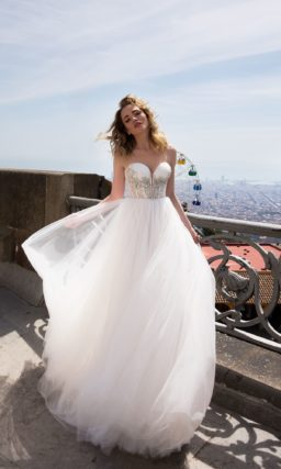 Свадебное платье с многослойной юбкой и открытым корсетом с декором из серебристых стразов.
