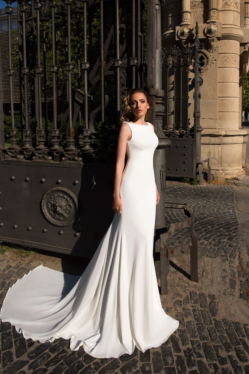 Лаконичное свадебное платье облегающего кроя из атласной ткани, с закрытым лифом и шлейфом.