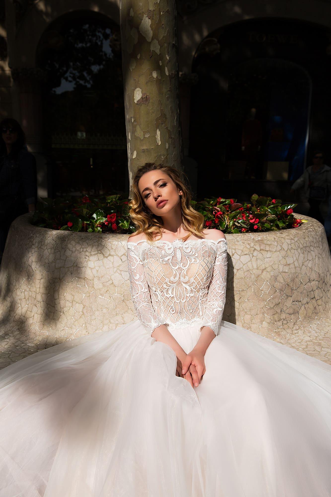 Романтичное свадебное платье с фигурным портретным декольте и прямой многослойной юбкой.