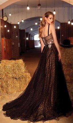 Необычное вечернее платье из черной ткани с юбкой А-силуэта, украшенной аппликациями.