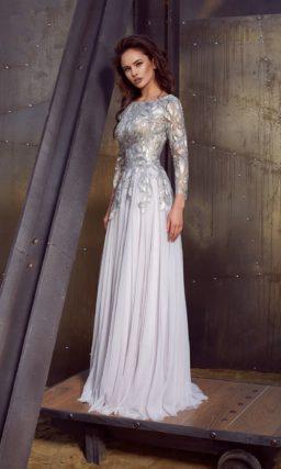 Прямое вечернее платье белого цвета с длинным облегающим рукавом и серебристой отделкой.