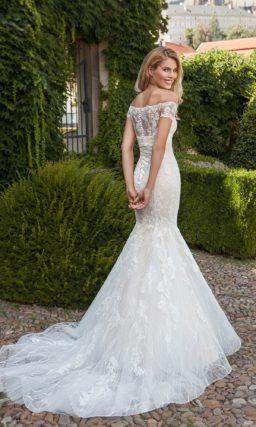 Романтичное свадебное платье «русалка» на бежевой подкладке, украшенное белым кружевом.