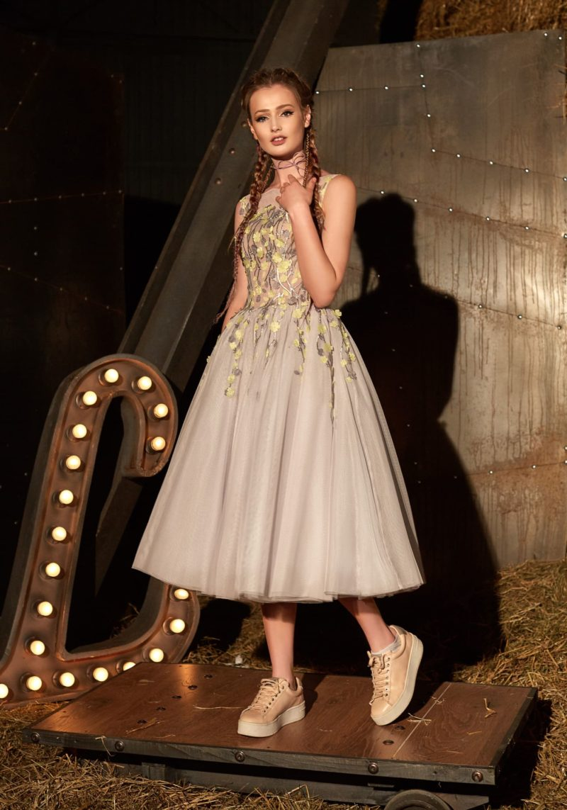 Бежевое вечернее платье с пышной юбкой длины миди и серо-желтой отделкой по лифу.