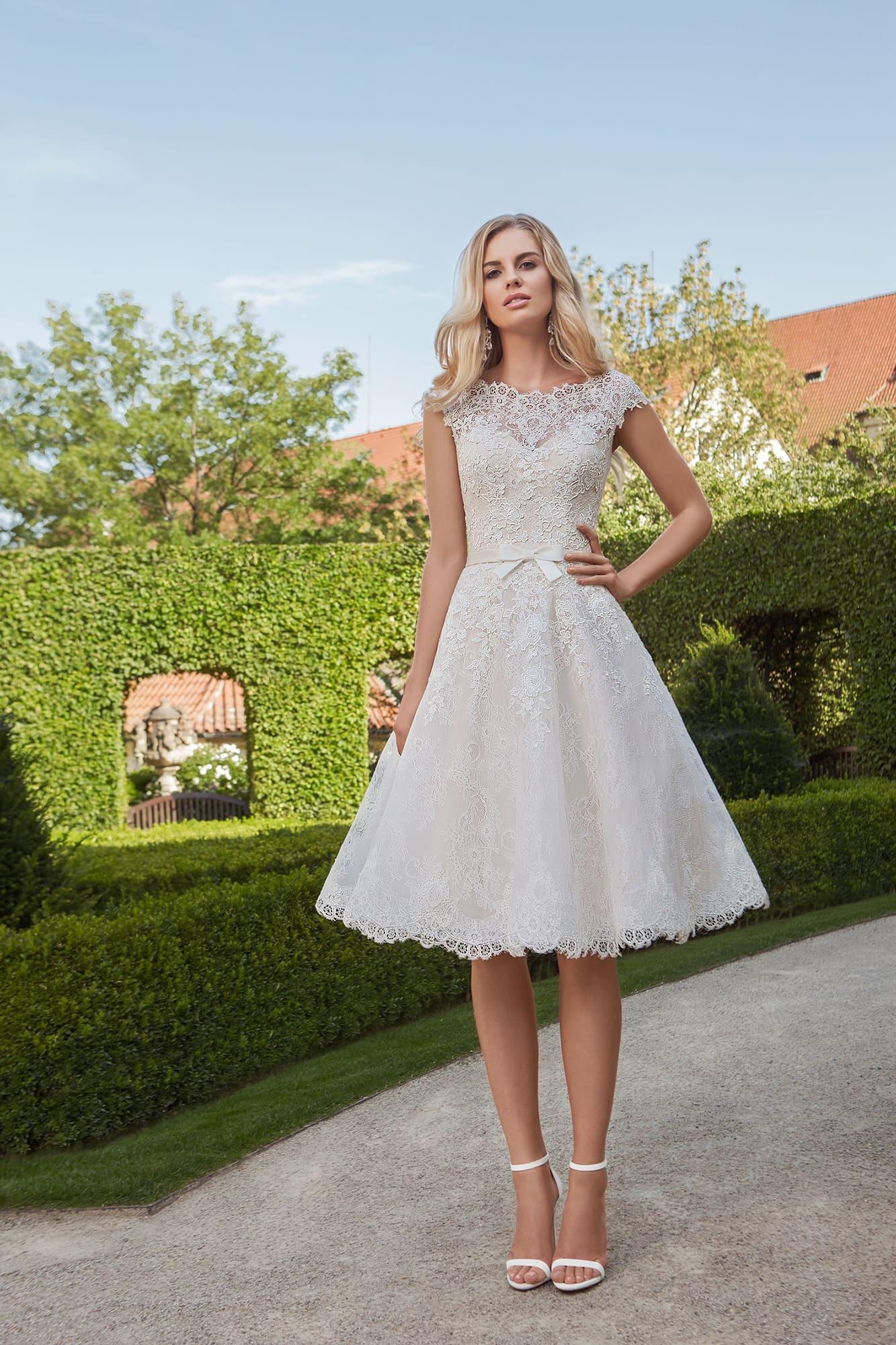 529a85984dd Кокетливое свадебное платье с кружевной отделкой и пышной юбкой длиной до  колена.