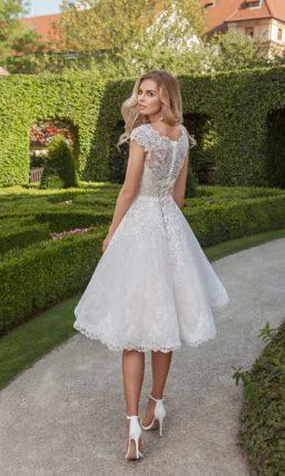 Кокетливое свадебное платье с кружевной отделкой и пышной юбкой длиной до колена.