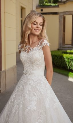Кружевное свадебное платье с тонкой вставкой над лифом и эффектной юбкой А-силуэта.