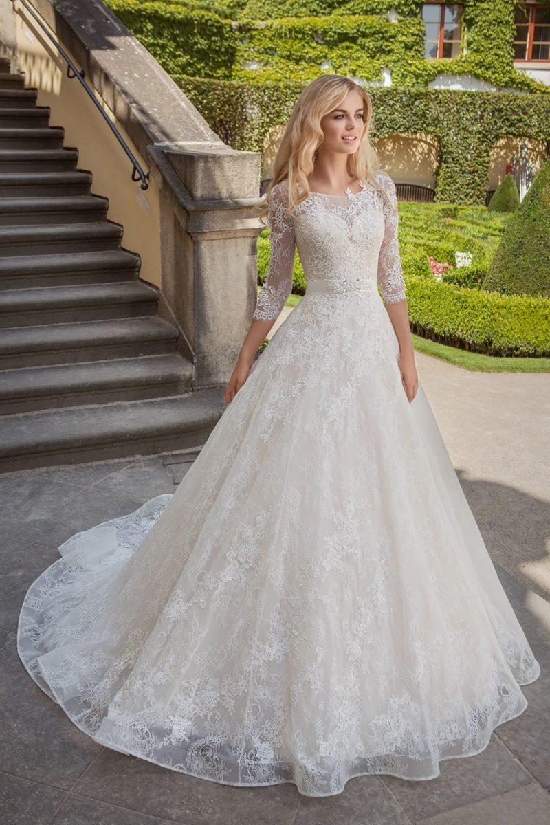 Кружевное свадебное платье с рукавами в три четверти и изящным округлым вырезом под горло.
